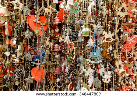 Lots of wooden Christmas ornaments hanging on ropes at a market in Vienna, Austria. - stock photo