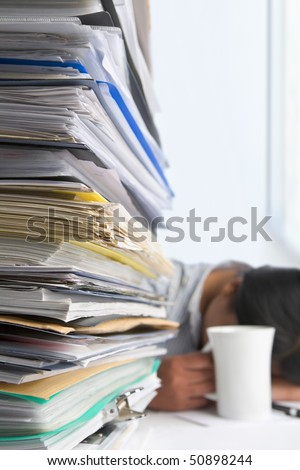 Lots of workload with people sleeping on background. PS: small depth of field and selective focus on papers - stock photo