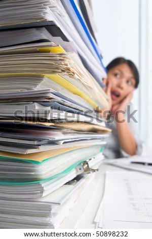 Lots of workload with people surprise on background. PS: small depth of field and selective focus on papers - stock photo