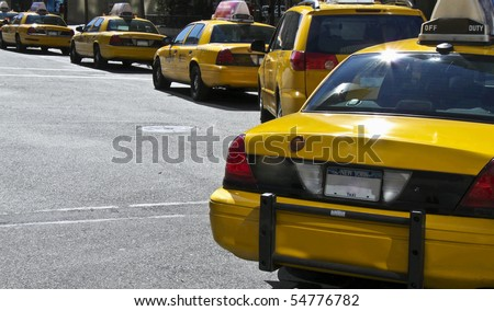 lots of yellow New York Taxis waiting on traffic lights
