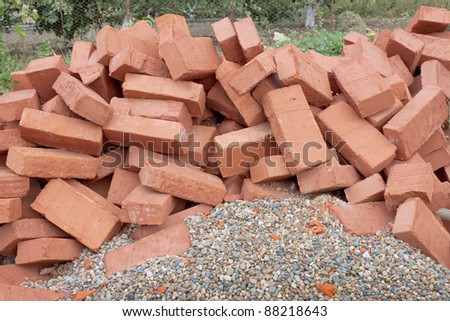 Lots red clay bricks lying on the gravel - stock photo