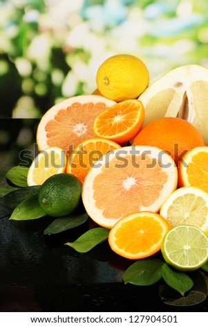 Lots ripe citrus on black table on natural background - stock photo
