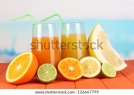 Lots ripe citrus with juices on wooden table on natural background