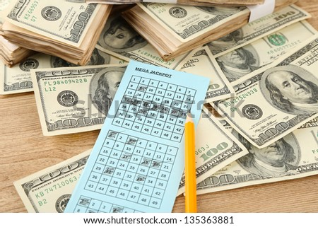 Lottery ticket,money and pencil on wooden background - stock photo