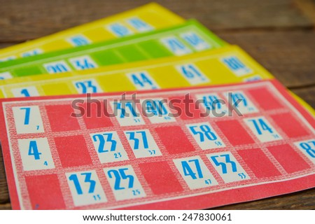 Lotto game colourful cards on wood background - stock photo