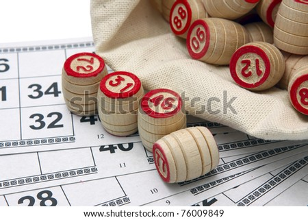 Lotto game: wooden kegs in a sack and game cards - stock photo