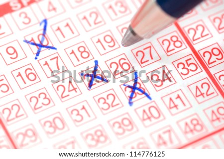 Lotto ticket with ticked numbers in selective focus - stock photo