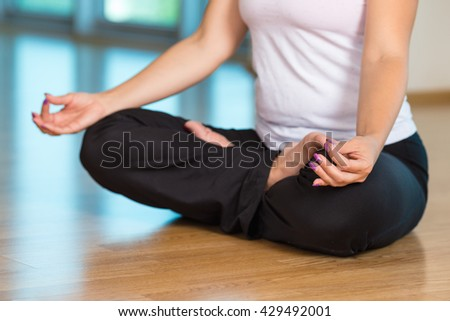 Lotus pose for yoga and a zen symbol with hands. Closeup of woman body in yoga pose