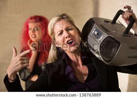 Loud mature woman with radio and cringing teenager - stock photo