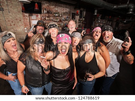 Loud motorcycle gang members with weapons and drinks - stock photo