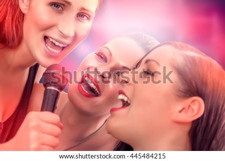loud singing girls in karaoke bar - stock photo