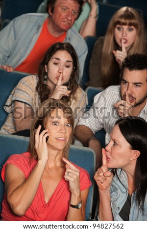 Loud woman on phone annoys people in theater - stock photo