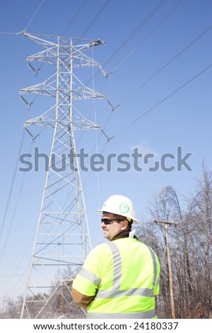 LOUISVILLE - 31 JANUARY: Pike Electric Supervisor, Tom Wallace, watches the work area as a worker repairs the top of a high tension line tower after ice damage from January 2009 storm. - stock photo