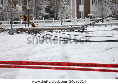 LOUISVILLE, KENTUCKY, 28 JANUARY: Electric utility pole brought down by weight of ice from storm blocking a road in the Douglass Hills neighborhood in Louisville, Kentucky, during a powerful storm on January 28, 2009. - stock photo