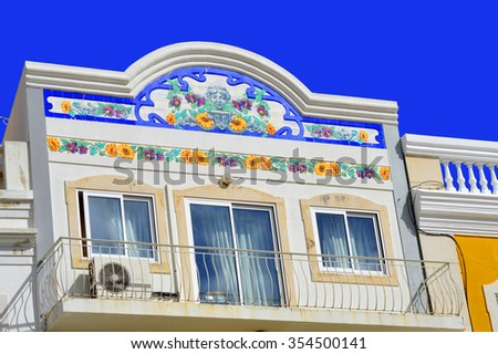 Loule, Algarve, Portugal - October 29, 2015 : Floral tiles on the front of a house with a balcony in Loule - stock photo
