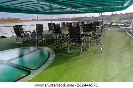 lounge and relax chairs on a cruise ship with a view of the Garonne River, Bordeaux (France) - stock photo