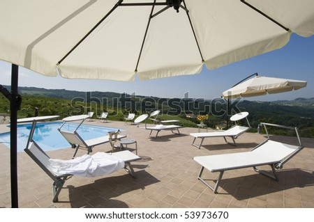 Lounge Chair And Umbrella Near The Swimming Pool