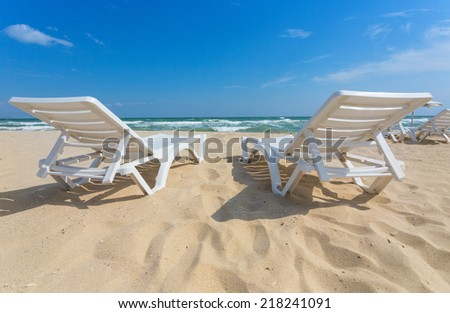 Lounge Chair On The Beach. Blue Sky And Sand.