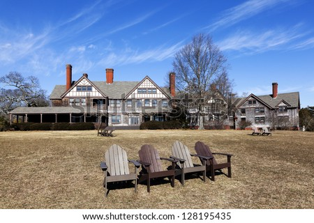 Lounge chairs and English country house.  The Mansion is Located at Bayard Cutting Arboretum State Park on Long Island, New York. - stock photo