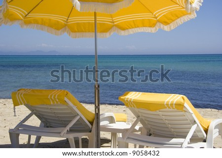 lounge chairs and parasol on the beach of saint-tropez - summer on the french riviera - stock photo