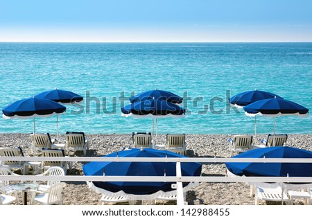 Lounge chairs and parasol on the beach, southern France - stock photo