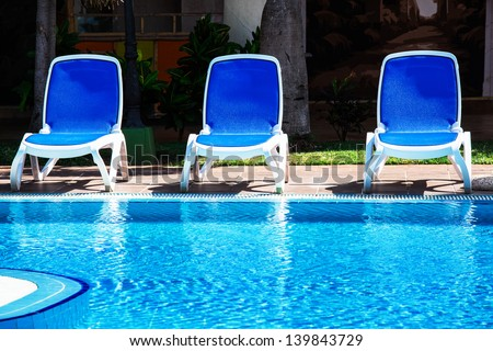 lounge chairs by the pool - stock photo