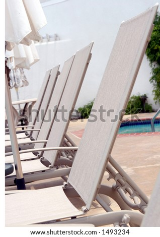 Lounge chairs by the pool #2. - stock photo