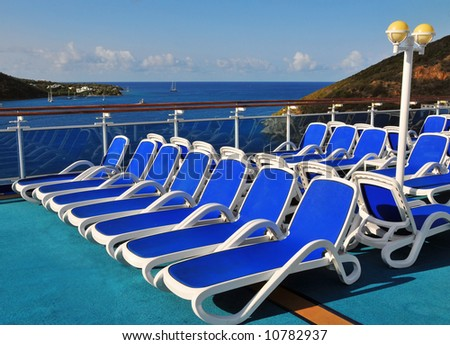 Lounge Chairs on a Deserted Cruise Ship Deck overlook a Tropical Island - stock photo