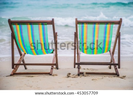Lounge chairs on a tropical beach at summer - stock photo