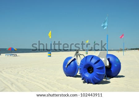 Lounge chairs, umbrellas, and oversized trikes scattered along Biloxi Beach in Mississippi on a spring day. - stock photo