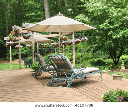 Lounge chairs under patio umbrella on deck decorated with hanging baskets of petunias - stock photo