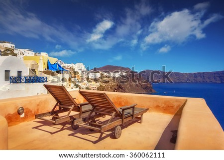 Lounge chairs with a view of the caldera, Oia village, Santorini, Greece - stock photo