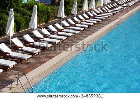 Lounge sunbeds near swimming pool - stock photo