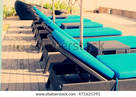 Lounge sunbeds near swimming pool at luxury hotel.
