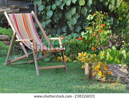 lounger chair in a garden with flower and patch  - stock photo