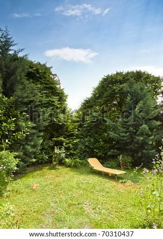 Lounger in a calm summer garden - stock photo