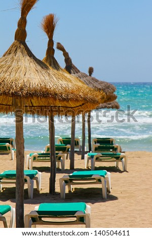 loungers and straw umbrellas on the beach - stock photo