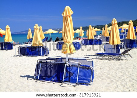 Loungers and umbrellas on the beach - stock photo