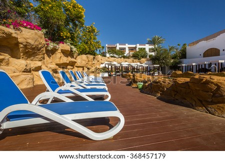 Loungers near the pool, luxury buildings and palm trees behind  - stock photo