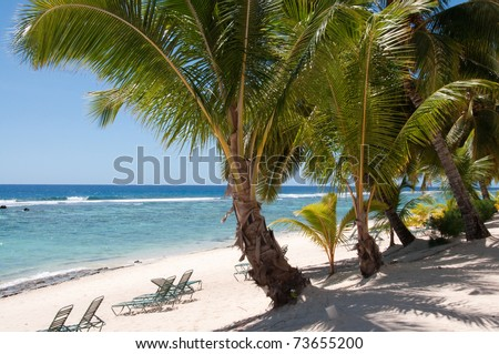 Loungers on the beach at a Cook Islands resort - stock photo