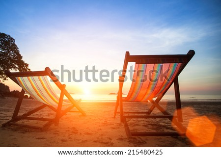Loungers on the beach deserted oceanside at amazing sunrise. - stock photo
