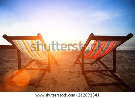 Loungers on the deserted coast sea at sunrise. - stock photo