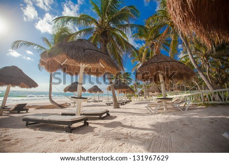 Lounges under an umbrella on sandy beach - stock photo