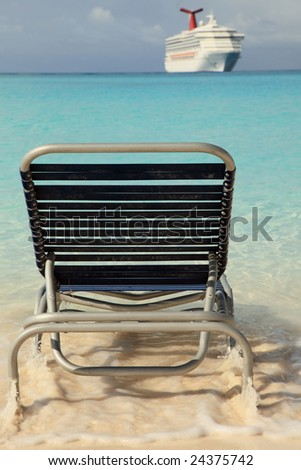 Lounging chair in the blue ocean with cruise ship in background