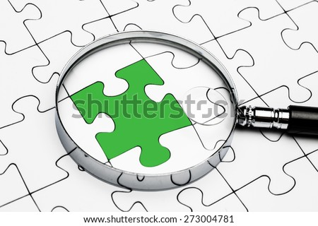 Loupe on jigsaw Jigsaw and puzzles concepts - stock photo