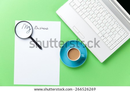 loupe, paper and cappuccino with computer on green background