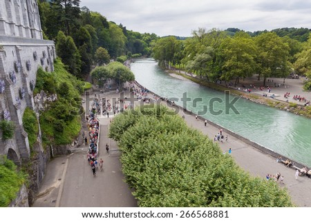 LOURDES, FRANCE - JULY 23, 2014: Overal view of the Cave of Massabielle at the Basilica in Lourdes. 5,000,000 pilgrims and tourists visit Lourdes every season. - stock photo