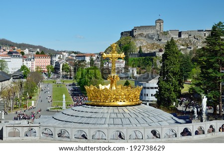 Lourdes is a major place of Roman Catholic pilgrimage. There is a dome of the Rosary basilica surmounted with the gilded crown and the cross in the foreground.