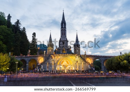 LOURDES - JULY 23, 2014: Pilgrims partaking in La Procession Mariale Aux Flambeaux or the Torchlight Marian Procession in Lourdes. The torchlight procession takes place at the Domain daily at 9.00pm. - stock photo