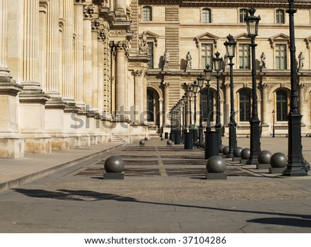 Louvre courtyard with lamps and pillars.